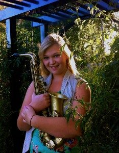 Kendra Heslip Holding Her Saxophone In A Garden